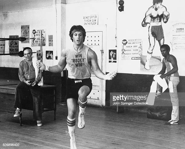 Training for a heavy weight title fight, Rocky Balboa skips rope under the watchful eye of his manager, Mickey , and trainer Johnny in Rocky II.