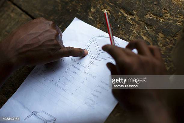 Training for carpenters at the vocational school Young Africa Hands pointing to a design drawing on September 29 2015 in Beira Mozambique