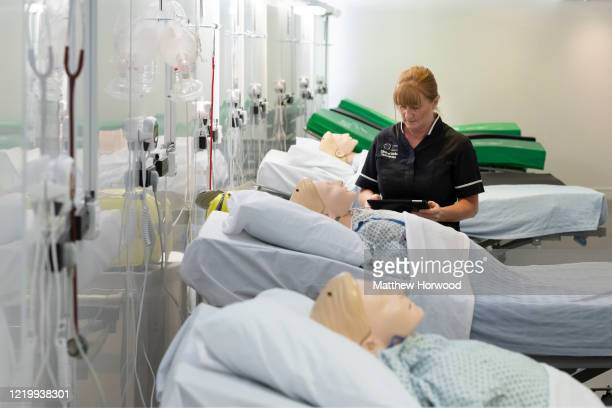 NHS training manager stands near a medical training mannequin which can be controlled using a computer on a ward at the new Dragon's Heart Hospital...