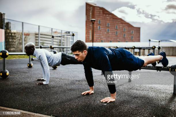 training outdoors on rainy day - diverse friends doing push ups after rain on wet ground. - only men stock pictures, royalty-free photos & images