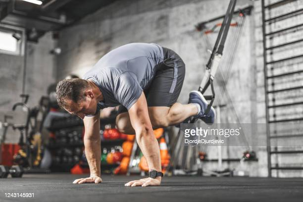 trx training, sports man doing abs exercise in a gym - mid adult stock pictures, royalty-free photos & images