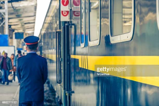 trainman standing beside green old train
