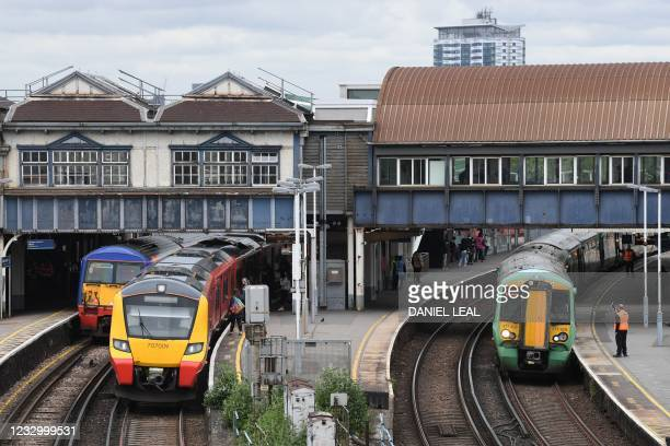 Trains arrive at Clapham Junction station in London on May 20, 2021. - Britain today unveiled long-awaited reforms of the country's railways,...