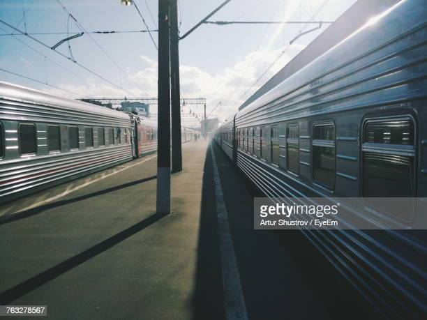trains at railroad station against sky - railroad station platform stock pictures, royalty-free photos & images
