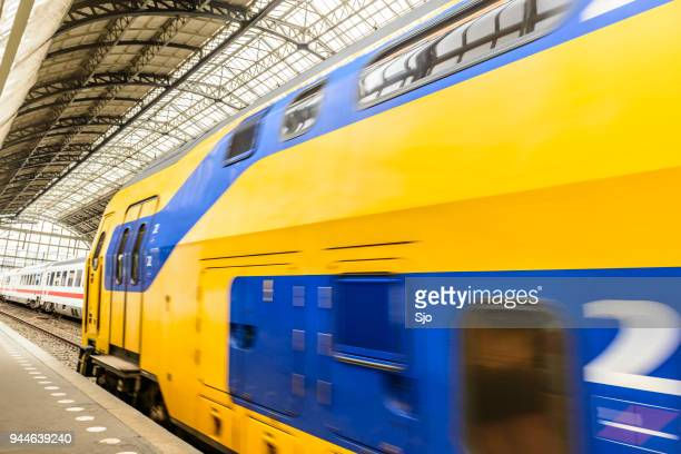 Trains on railway tracks in Amsterdam Central Station. An intercity dubbledecker of the Dutch Railways (NS) is departing.