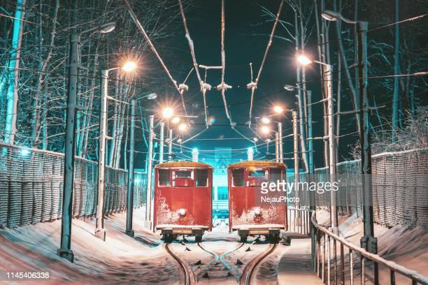 trains on snow covered railroad tracks amidst illuminated street lights at night - lituania fotografías e imágenes de stock