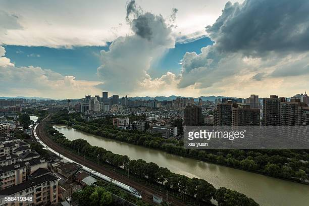 Trains passing on buildings in downtown Hangzhou with storm clouds,China