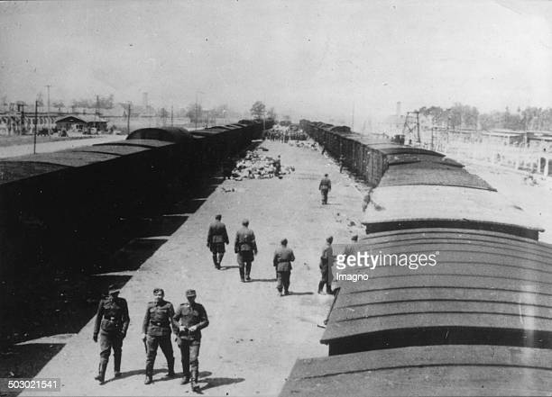 Trainstation of the concentration camp Auschwitz/Birkenau. Poland. In the background can be seen the crematoria No. 1 and No. 2. Photograph. 1944. .