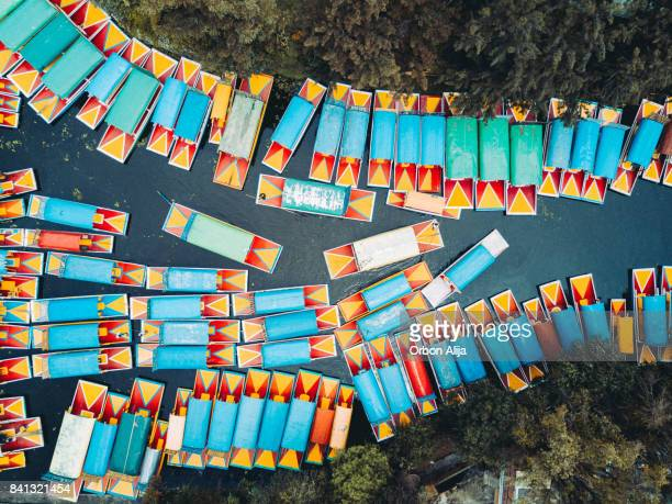 'trajinera' boats in the xochimilco's canals, mexico city. - mexico city stock pictures, royalty-free photos & images