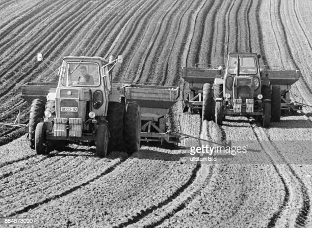 Traktoren mit Kartoffellegemaschinen auf einem Feld 1975