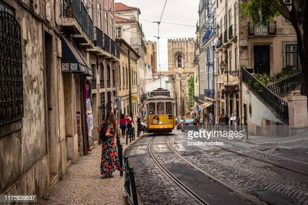 tram 28 vervoert toeristen door de wijk alfama in lissabon, portugal - tram stockfoto's en -beelden