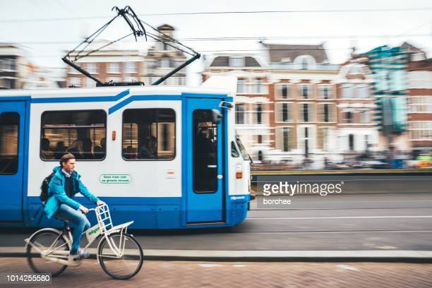 tram and cyclist in amsterdam - cable car stock pictures, royalty-free photos & images