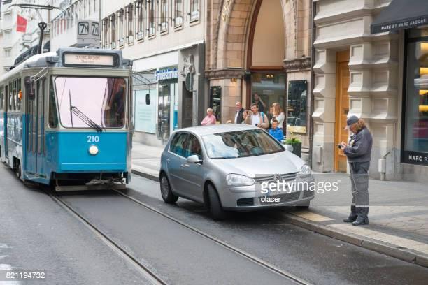 Tram et une voiture garée en difficulté