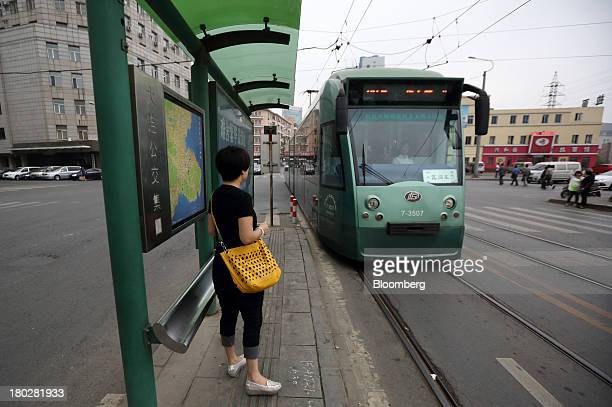 A tram approaches a tram stop as a passenger waits in Dalian China on Tuesday Sept 10 2013 Goldman Sachs Group Inc last week raised its estimate for...