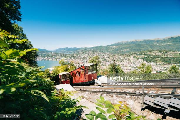Tram ascending mountain, alpine lake and city below