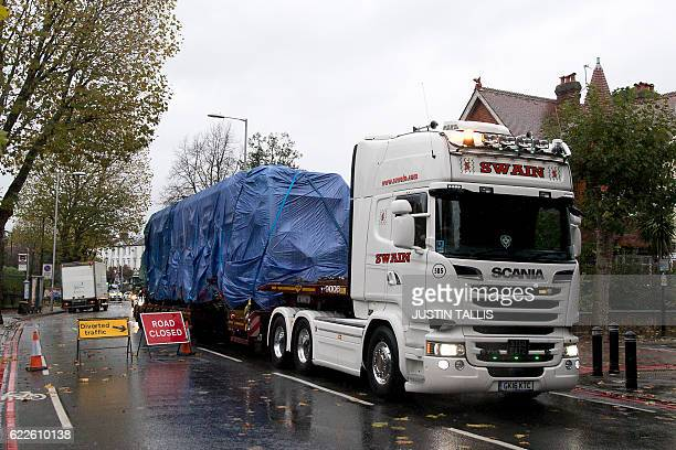A tram carriage covered in tarpaulin is driven away from the scene of the accident on a truck in Croydon south London on November 12 2016 At least...