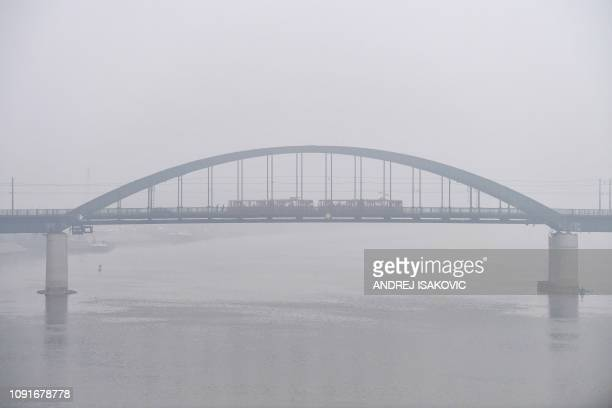 Tram crosses a bridge over the Sava river in Belgrade, on January 31 as heavy fog and air pollution dominate the sky over Serbian capital Belgrade.