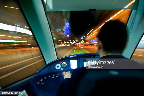 tram driver driving tram at night, rear view, blurred motion - tram stockfoto's en -beelden