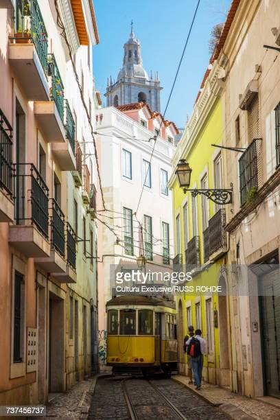 Tram in narrow street, Alfama District, Lisbon, Portugal