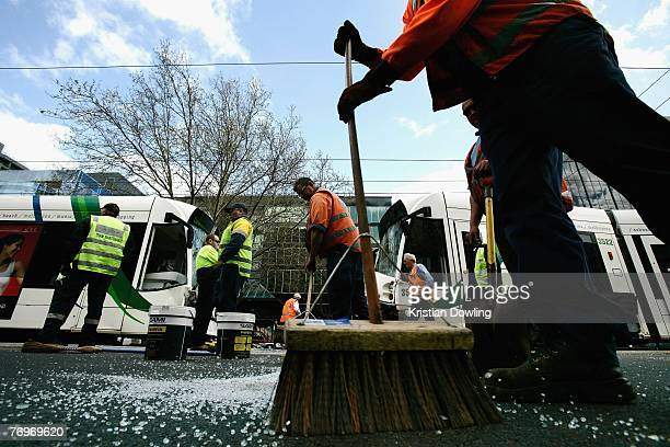 A tram maintenance worker sweeps away pieces of broken glass following a collision between a car and two trams on St Kilda Road on September 24 2007...