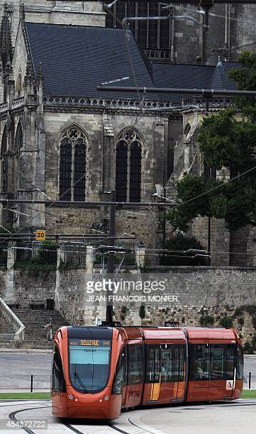 A tram moves along a track past the Saint Julien Cathedral in Le Mans on August 30 2014 The second tramline of Le Mans was put into service after...