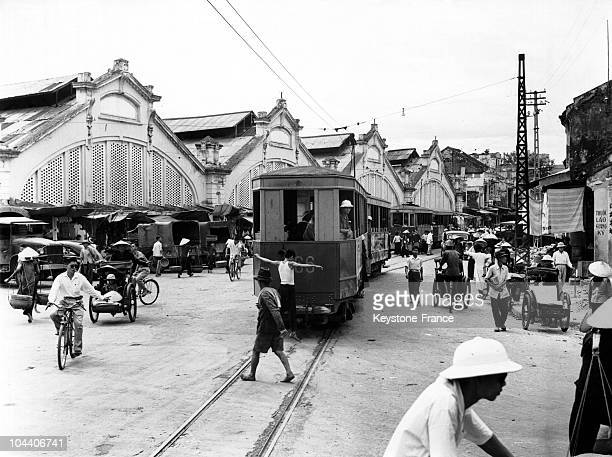 A tram runs before the great central market of modern design in Hanoi Indochina in the 1950's