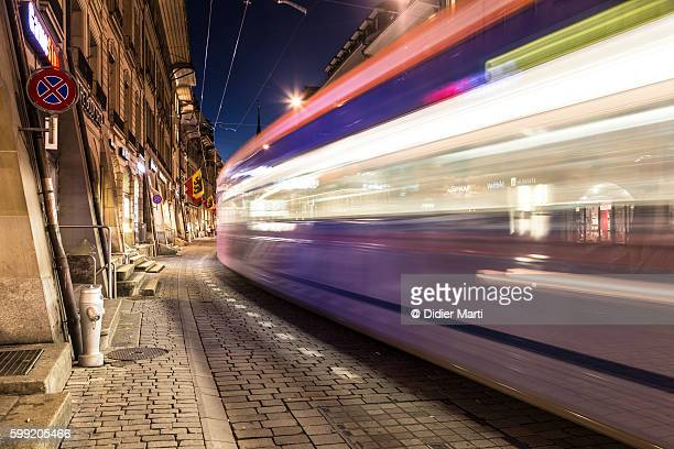 A tram rushes at night in the street of Berne