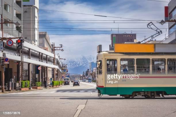a tram train passing the street in toyama city - 富山県 ストックフォトと画像