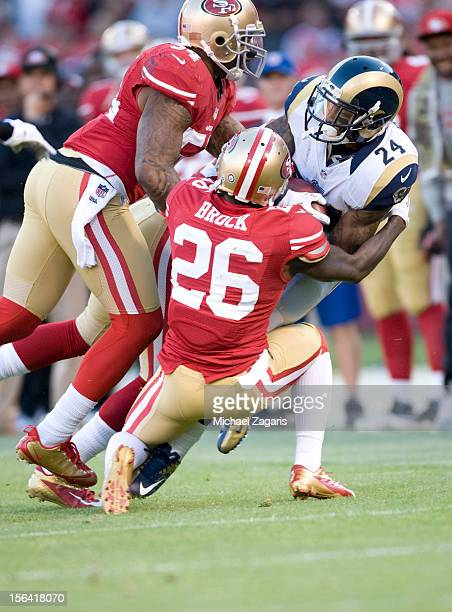 Tramaine Brock and Larry Grant of the San Francisco 49ers strip the ball from Isaiah Pead of the St Louis Rams during the game at Candlestick Park on...
