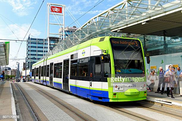 tramlink tram stops outside east croydon railway station - tram stock photos and pictures