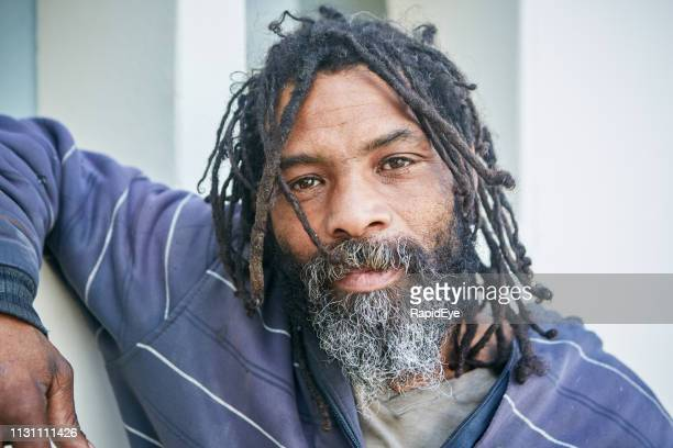 tramp with rastafarian dreadlocks looks at camera, thinking - homeless person stock pictures, royalty-free photos & images