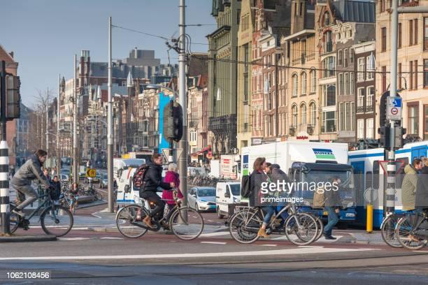 straßenbahnen und reisende vor amsterdam hauptbahnhof (ed) - pedalantrieb stock-fotos und bilder