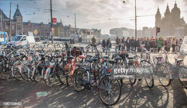 trams and travellers in front of amsterdam central railway station (ed) - image title stock pictures, royalty-free photos & images