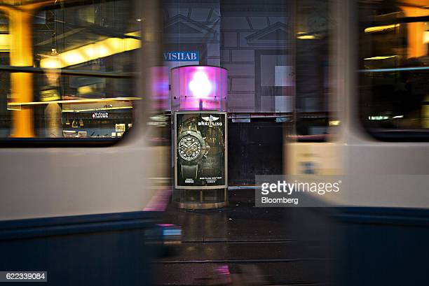Trams pass an illuminated Breitling SA luxury watch advertisement in Zurich Switzerland on Wednesday Nov 9 2016 Donald Trump's ascendancy to the...