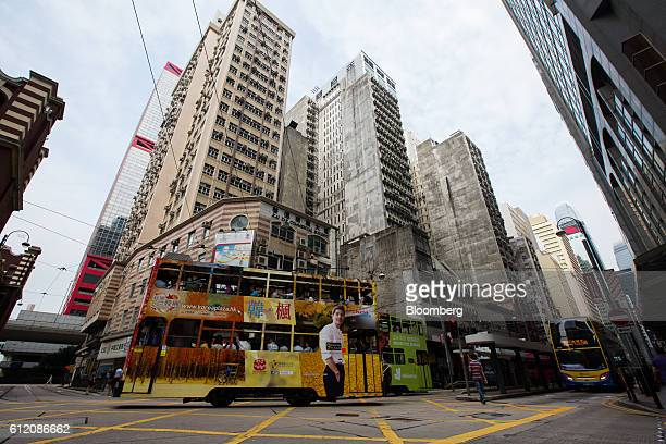 Trams travel past residential buildings in the Sheung Wan district of Hong Kong, China, on Thursday, Sept. 29, 2016. Hong Kong faces growing...