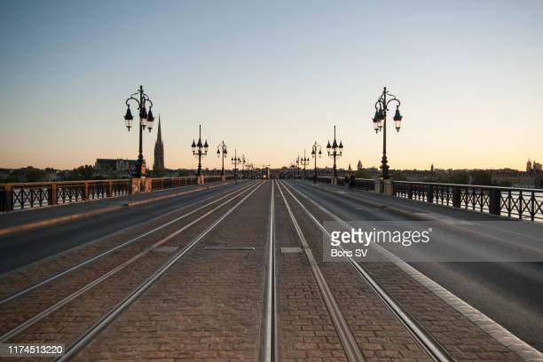 tramway on stone bridge in bordeaux, france - street light stock pictures, royalty-free photos & images
