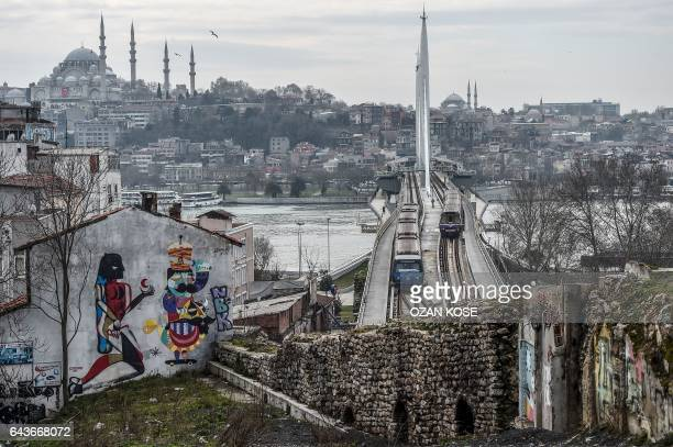 Tramways cross the Halic bridge as the Suleymaniye mosque is seen in the background on February 22 2017 in Istanbul / AFP / OZAN KOSE