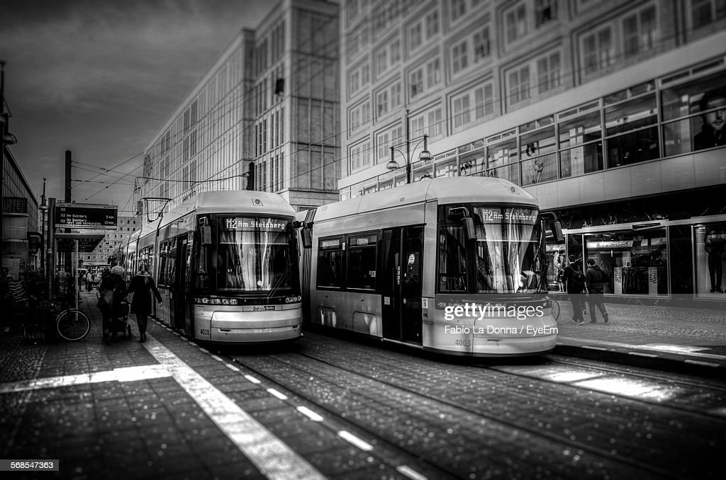 Tramways Moving On Street By Buildings Against Sky : Stock Photo