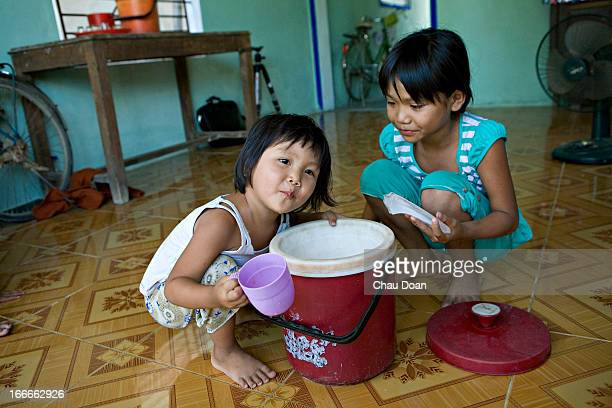 Tran My Duyen left and Tran Thi Thuy Van right granddaughters of the family head Tran Van Doc drink water in their house in Dong Lam hamlet near Dai...