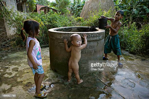 Tran Quoc Xuong right bathes while a neighbour's children play at the hamlet well in Dong Lam hamlet near Dai Quang Quang Nam province