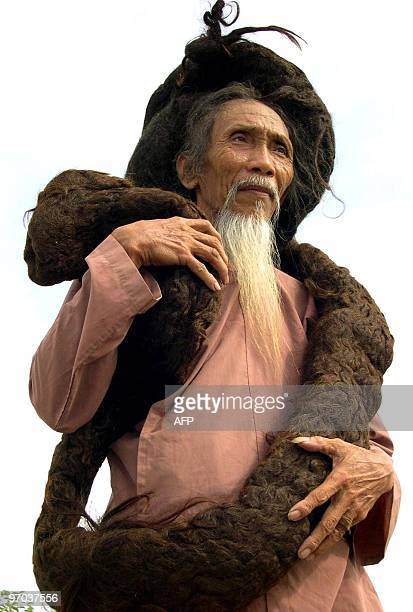 Tran Van Hay from the Chau Thanh district in southern Kien Giang province, poses while showing his over 6.2-meter long hair, 19 June 2004, in the...