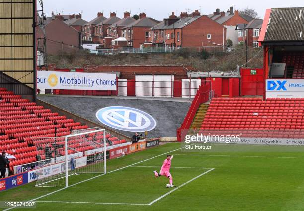 Tranmere goalkeeper Scott Davies in a pink kit, takes a goal kick as nearby houses are pictured outside of the ground during the FA Cup Third Round...