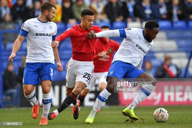 Tranmere Rovers' Cameroonian defender Manny Monthe shields the ball from Manchester United's English striker Mason Greenwood during the English FA...
