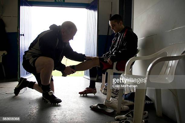 Tranmere Rovers' club physio Les Parry attending to an injured youth team player during a training session at the club's training ground at Raby Mere...