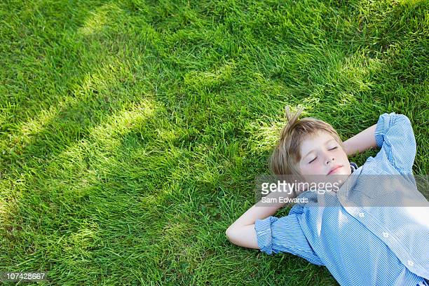 Tranquil boy napping in grass