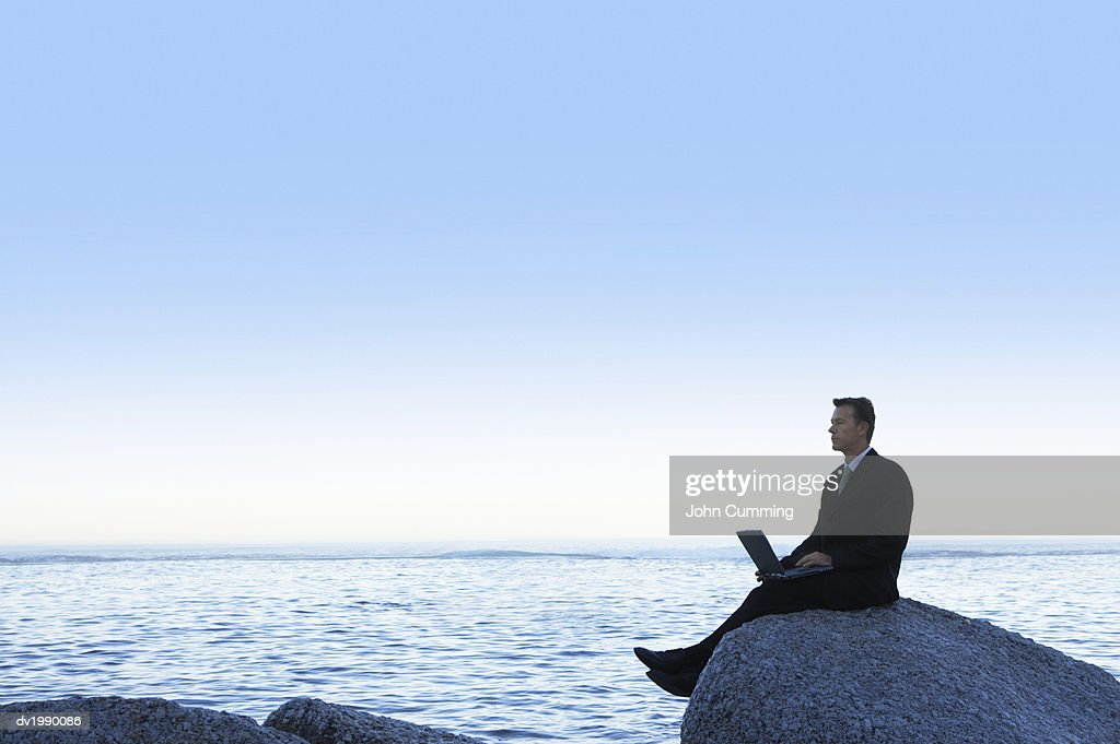 Tranquil Businessman Sitting on a Rock by the Sea and Using a Laptop Computer : Stock Photo