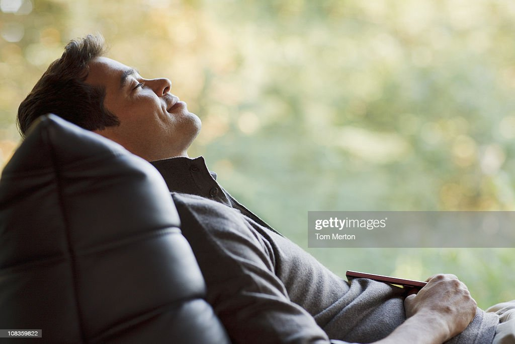 Tranquil man napping in chair : Stock Photo