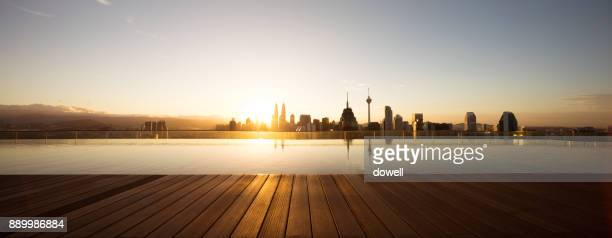tranquil pool and cityscape of modern city at sunrise