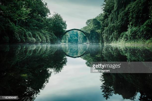 tranquil rakotzbruecke devils bridge, rakotzbruecke, brandenburg, germany - boog architectonisch element stockfoto's en -beelden