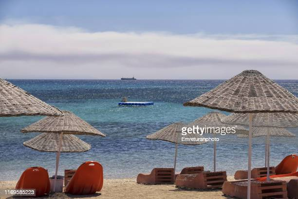 tranquil sand beach with sunshades. - emreturanphoto stock pictures, royalty-free photos & images